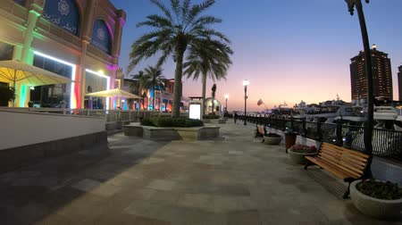 porto arabia : Doha, Qatar - February 18, 2019:Benches and palm trees along marina walkway in Porto Arabia at Pearl-Qatar with skyscrapers of West Bay skyline at blue hour.Scenic sunset of Persian Gulf, Middle East