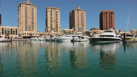 porto arabia : Marina corniche promenade in Porto Arabia at the Pearl-Qatar, Doha, with residential towers and luxury boats and yachts in Persian Gulf, Middle East. Sunny day, blue sky.