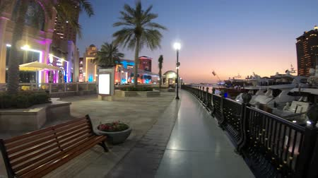 porto arabia : Doha, Qatar - February 18, 2019:Benches and palm trees along marina walkway in Porto Arabia at the Pearl-Qatar, Doha West Bay skyline illuminated at blue hour.Scenic sunset of Middle East Persian Gulf