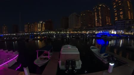docked : Doha, Qatar - February 18, 2019:Luxurious yachts and boats at Porto Arabia Marina at night. The Pearl-Qatar in Doha artificial island and a popular tourist destination in Persian Gulf, Middle East.