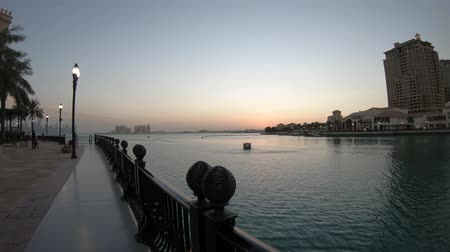 porto arabia : Marina corniche promenade at twilight in Porto Arabia at the Pearl-Qatar, Doha, with residential towers and luxury boats and yachts in Persian Gulf, Middle East.