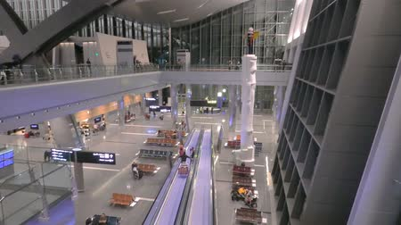 arabian peninsula : Doha, Qatar - February 24, 2019: aerial view of interior lobby and escalator of Hamad International Airport or Doha Hamad Airport, the only airport in Qatar open to civilian traffic, opened in 2014.