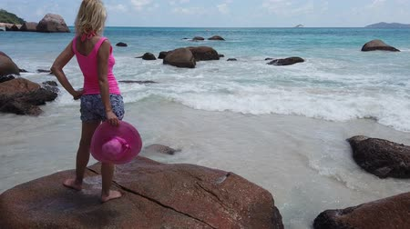 praslin : Lifestyle female in sunhat standing on a large granite boulder in popular Anse Lazio beach. Carefree woman looking turquoise Indian ocean on Praslin Island, Seychelles. Sunny beautiful sky.