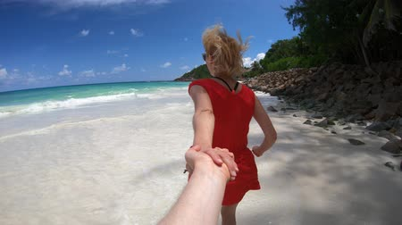 anse : Follow me. Happy tourist woman in red dress, holding her man hand at Seychelles, Indian Ocean. Beautiful pristine beach, turquoise sea. Wild Anse Kerlan, southwest Praslin. Tropical summer holidays Stock Footage