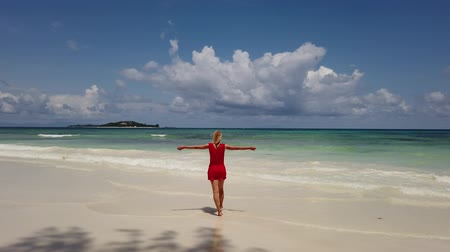 praslin : Elegant lifestyle woman in red dress at Anse Kerlan, Seychelles walking. Kerlan Beach in Praslin is famous for spectacular sunsets on Cousine and Cousin islands. Luxury holidays