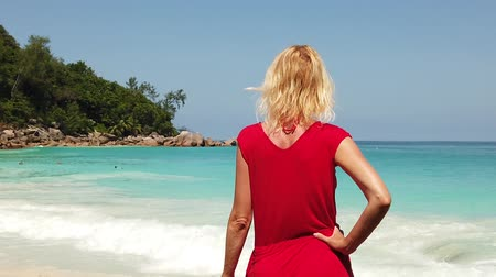 bum : SLOW MOTION: Lifestyle female in red dress in Anse Georgette. Elegant woman looking turquoise sea in Praslin Island, Seychelles. Blue sky, copy space.