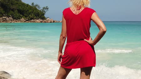солнечные ванны : SLOW MOTION: Summer holidays in Seychelles.Caucasian female in red dress sunbathes at Anse Georgette, one of most beautiful beaches of north of Praslin. Carefree lifestyle woman on paradise beach Стоковые видеозаписи