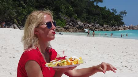 exotic dishes : SLOW MOTION: Healthy exotic summer diet. Attractive woman in red dress holding fresh fruit dish at Anse Georgette, Praslin with turquoise sea and palm trees. Happy lifestyle female at Seychelles.