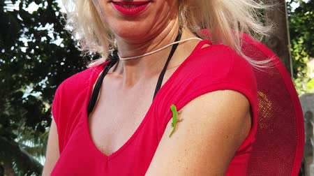 enjoys : Blonde woman with a cute Phelsuma sundbergi, La Digue day gecko on her arm at Seychelles. Blonde female enjoys with a lizard, wildlife of La Digue. Palm trees background. SLOW MOTION