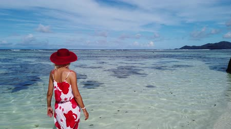 águas : Tourist woman in red hat walking in the sea at Anse Source dArgent. Elegant female looks turquoise sea of Indian ocean on La Digue Island, Seychelles.Aerial view of tropical beach, scenic landscape