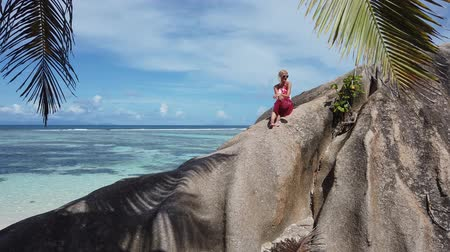 waters : Summer in La Digue, Seychelle. Carefree tourist woman with red hat sitting on a huge granite boulder at Anse Source dArgent. Female lifestyle above big rocks with turquoise sea and palm leaves.