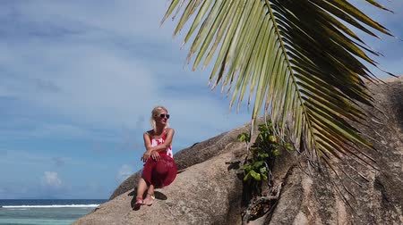águas : La Digue, Seychelle. Lifestyle tourist woman in red above a huge granite boulder at Anse Source dArgent. Big rocks and turquoise sea of Source dArgent, most beautiful beach in the world. SLOW MOTION