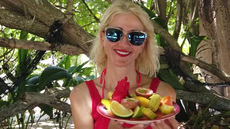 exotic dishes : SLOW MOTION:Tourist woman with fresh local fruit dish at Anse Source dArgent, La Digue under palm trees. Lifestyle female enjoy on tropical beach at Seychelles. Healthy exotic summer diet.