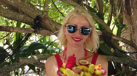 anse : SLOW MOTION:Healthy exotic summer diet. Tourist woman in red dress holding fresh fruit dish at Anse Source dArgent, La Digue under palm trees.Lifestyle female enjoys on tropical beach at Seychelles