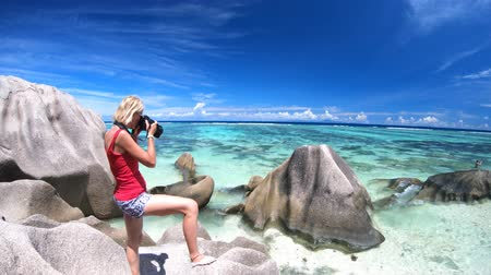 kei : Lifestyle blonde woman photographer with camera at Anse Source dArgent, La Digue, Seychelles. Shallow waters, pristine sand, turquoise sea and shaped boulders. Summer tropical holiday destination. Stockvideo