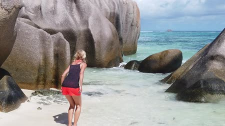 anse : SLOW MOTION: backside young woman jumping on seashore of Anse Source DArgent, the most beautiful beach in the world. Joyful tourist on paradise beach Indian Ocean. La Digue, Seychelles with blue sky. Stock Footage