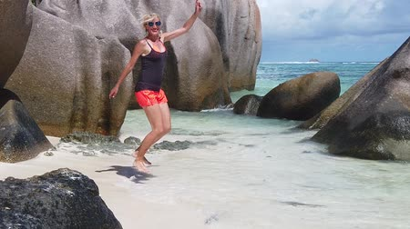 enjoys : La Digue, Seychelles: carefree freedom young woman jumping on seashore of Anse Source DArgent, most beautiful beach of world. Joyful tourist on paradise beach Indian Ocean and blue sky. SLOW MOTION