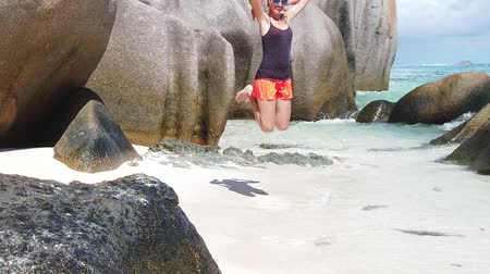 ugró : La Digue, Seychelles SLOW MOTION: Joyful tourist on paradise beach Indian Ocean and blue carefree freedom young woman jumping on seashore of Anse Source DArgent, most beautiful beach of world. sky.