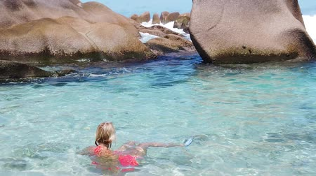 anse : SLOW MOTION: Blonde tourist woman in orange bikini at Anse Marron in the natural pools. La Digue, Indian Ocean. Young girl enjoying at Seychelles. Stock Footage
