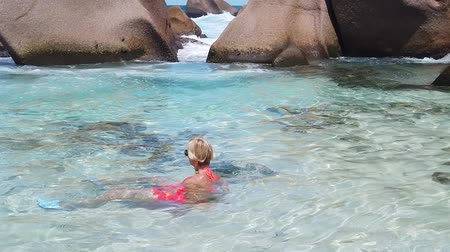 boulders : SLOW MOTION: La Digue, Anse Marron, swimming pool. Attractive woman in bikini lying on crystal water Anse Marron protected by huge rock formations. Scenic landscape of secret beach at Seychelles.