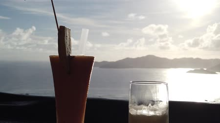 seychely : Fruit cocktail and glass of beer at sunset light. Spectacular view of Indian Ocean and Praslin Island from top view of La Digue, Seychelles. SLOW MOTION