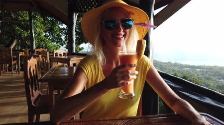 praslin : Happy tourist woman in yellow dress drinks fruit cocktail from top view of La Digue. Lifestyle female enjoying spectacular views of Praslin Island, Seychelles and Indian Ocean. Sunset light. Stock Footage