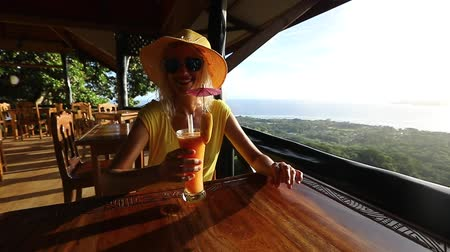cheers : La Digue appetizer from highest of island at sunset. Lifestyle female enjoying spectacular views of Seychelles and Indian Ocean.Elegant tourist woman in yellow dress drinking cocktail in SLOW MOTION
