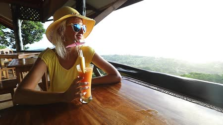 tropy : SLOW MOTION: Carefree lifestyle female enjoying spectacular views of Seychelles and Indian Ocean at sunset. Elegant woman in yellow heaving appetizer with Praslin aerial view from La Digue Island top.
