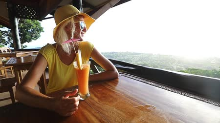 наивысший : SLOW MOTION: Tourist woman in yellow dress with appetizer cocktail at Seychelles, Indian Ocean. Spectacular views of Praslin from top view of La Digue at sunset. Tropical summer holidays people. Стоковые видеозаписи