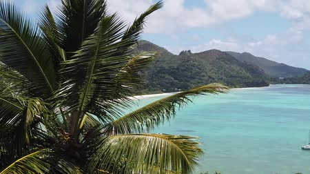 waters : SLOW MOTION: Tropical luxury destination. Panorama of Anse Gouvernement with turquoise sea, Praslin, Seychelles. Overlook Cote dOr Bay. Stock Footage