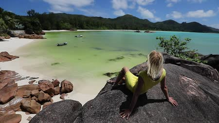 waters : Panorama of Praslin, Seychelles. Lifestyle tourist woman on granite boulder at Anse Gouvernement with tropical sea and pristine beach near Cote dOr Bay.Tropical summer holidays. SLOW MOTION
