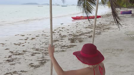 cote : SLOW MOTION: Lifestyle female enjoying in summer holidays swinging on tropical beach under coconut palm trees of Anse Volbert Cote dOr, Praslin, Seychelles, Indian Ocean.