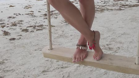 anse : SLOW MOTION: woman legs and feet with anklet on wooden swing in Anse Volbert Cote dOr beach , Praslin, Seychelles, Indian Ocean. close up