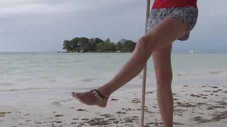 seychely : Blonde woman swinging legs on beach swing Anse Volbert Cote dOr, Praslin, Seychelles, Indian Ocean. Islet of Chauve Souris on background. Lifestyle female funny, summer vacation. SLOW MOTION Dostupné videozáznamy