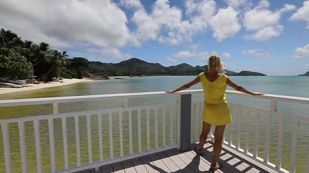 praslin : Lifestyle woman in yellow at balcony of wooden jetty, looking pristine white beach of Anse Gouvernement in Praslin, Seychelles near Cote dOr Bay. Elegant tourist in tropical destination. SLOW MOTION