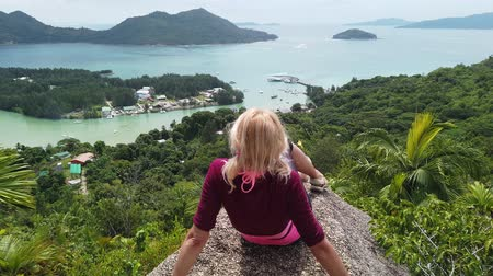 seychely : Tourist woman relaxing at lookout of Praslin after trekking inside Reserve of Fond Ferdinand. Scenic view from top view of Praslin on Bay of St. Anne. Amazing views of Seychelles and Indian Ocean.