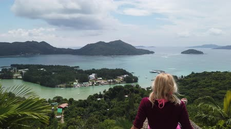 praslin : Amazing panorama of Seychelles Indian Ocean. Carefree tourist woman sitting at lookout of Praslin after trekking inside Reserve of Fond Ferdinand. Scenic view from top of Praslin on Bay of St. Anne.