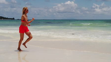 praslin : SLOW MOTION: Carefree woman in bikini running on seashore of Anse Kerlan. Wellness tourist on pristine sand, Indian Ocean. Kerlan Beach in Praslin island, Seychelles tropical summer holidays.