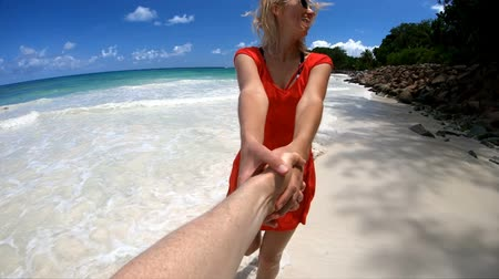 anse : SLOW MOTION Follow me. Blonde woman holding hand of her partner at Praslin, Seychelles, Indian Ocean. Famous travel destination of Anse Kerlan Beach and turquoise sea on background. Summer holidays.