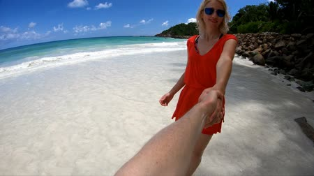 anse : SLOW MOTION Tropical summer holidays. Follow me POV. Tourist woman holding hand of boyfriend at Praslin, Seychelles, Indian Ocean. Popular destination of pristine Anse Kerlan Beach and turquoise sea