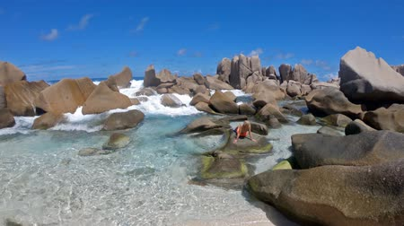 anse : La Digue, Anse Marron, natural pool. Attractive woman in bikini Relaxing on boulders of Anse Marron with huge rock formations. Scenic landscape of secret beach at Seychelles.