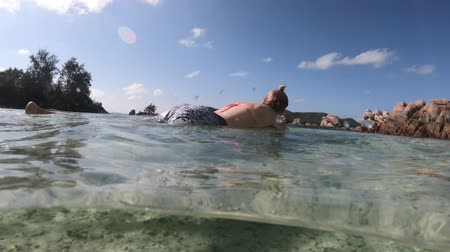 enjoys : Split view of woman sunbathing and relaxing on mattress with underwater part in the sea of Anse Takamaka, Praslin, Seychelles, Indian Ocean. Summer travel vacation. Under and above water photography.