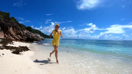 anse : SLOW MOTION: Lifestyle woman running by the sea on pristine white beach of remote Anse La Blague, southeast of Praslin Island, Seychelles. Tourist woman on tropical holiday.
