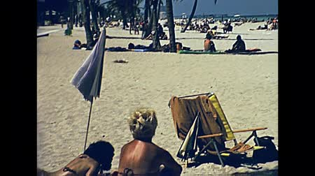 семидесятые годы : Miami Beach, Florida, United States - 1979: Beach of Miami and its tropical sea. Popular seafront street with palms in 70s with tourists catching tan. Historical United States of America. Стоковые видеозаписи