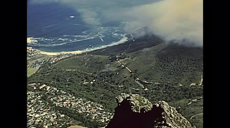 столовая гора : Aerial view of Cape Town city skyline, harbour and cliff from Table Mountain NP nature reserve, top of the mountain with cityscape. Historical archival footage in Cape Town city of 1980s South Africa
