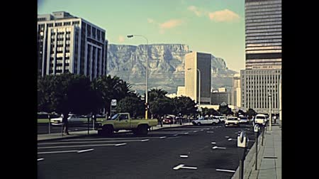 столовая гора : CAPE TOWN, South Africa - CIRCA 1980: street view with vintage cars in the city traffic. Table Mountain national park on background. Historical archival footage in Cape Town city of 1980 South Africa. Стоковые видеозаписи