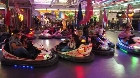 bumps : Province of Bologna, Italy - June 8, 2019: Children and young people playing driving wild bumper cars, in the Amusement Park night arena and crashing each other. Cars with European contries flags. Stock Footage