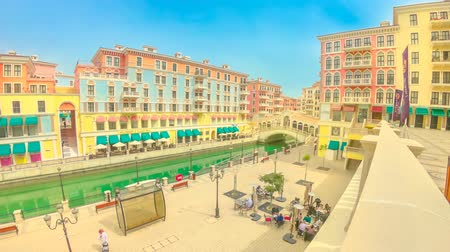 east pearl : Doha, Qatar - February 16, 2019: TIME LAPSE aerial of Venetian Rialto bridge and canal at picturesque district of Doha. Venice at Qanat Quartier in the Pearl, Persian Gulf, Middle East.