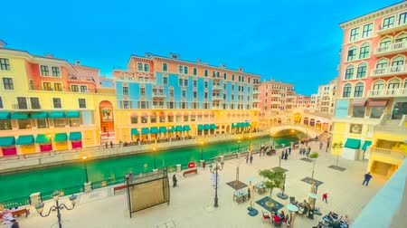Венеция : Doha, Qatar - February 16, 2019: TIME LAPSE aerial view of Venetian Rialto bridge with canal at picturesque district of Doha. Venice at Qanat Quartier in the Pearl, Persian Gulf, Middle East.