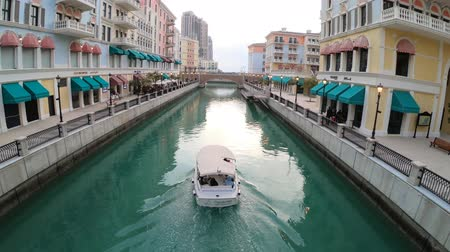 모터 보트 : Doha, Qatar - February 20, 2019: aerial view of cruise boat in little Venice with canals in venetian style. Colorful houses in picturesque Qanat Quartier icon of Doha. Venice at the Pearl district